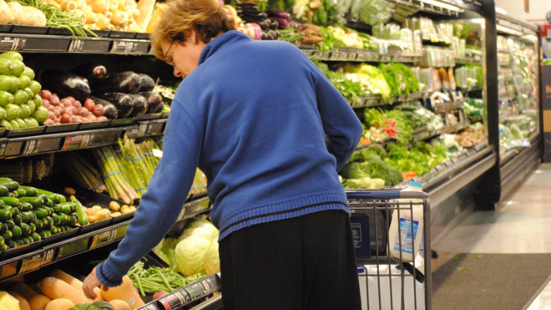 woman in blue shirt standing in front of the produce in a grocery store