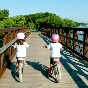 two children on bicycles riding across a foot bridge