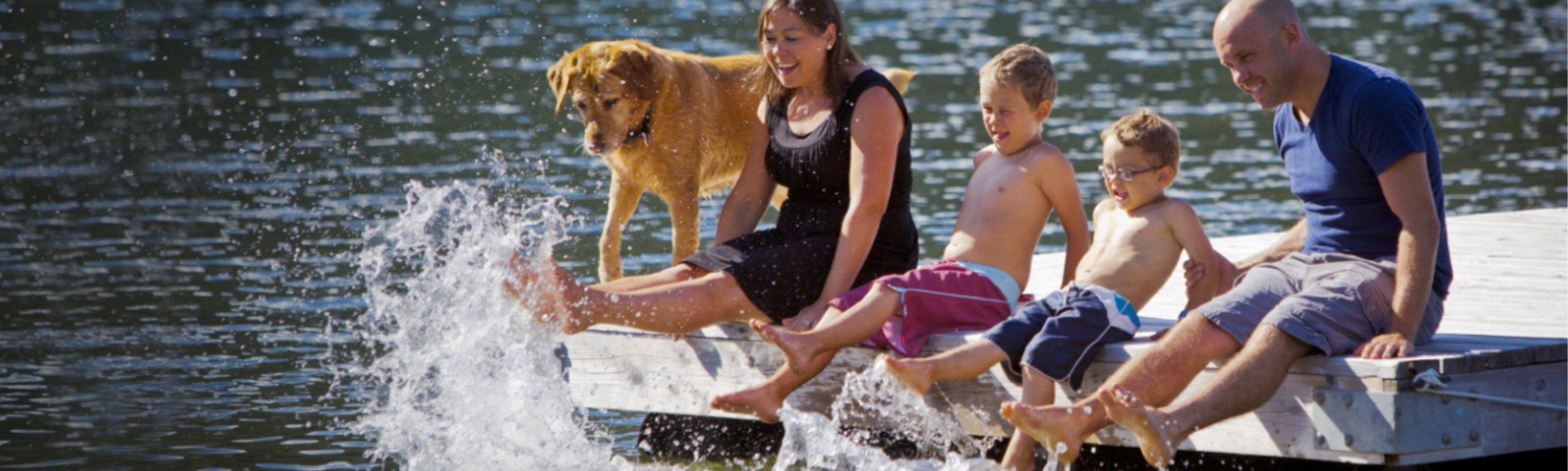 Family with dog at a lake on a swimming dock