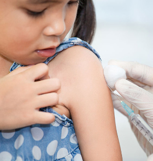 Little girl getting a shot in her arm