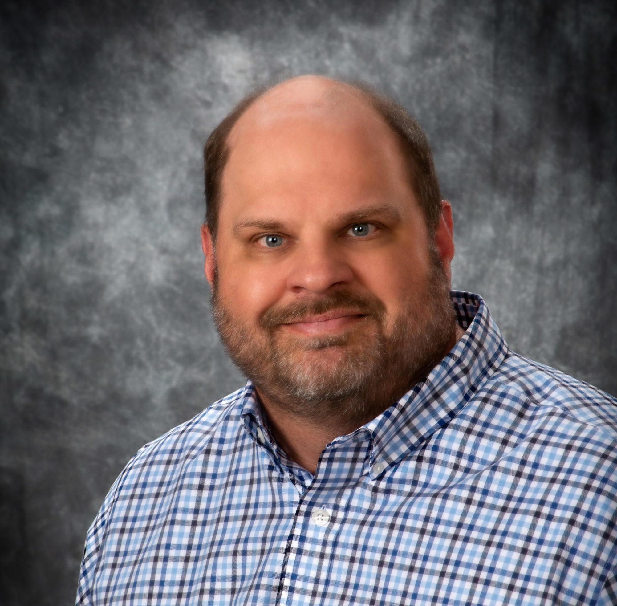 Dr. Jeremy Bolluyt, smiling at camera, wearing a blue plaid, button-down shirt.