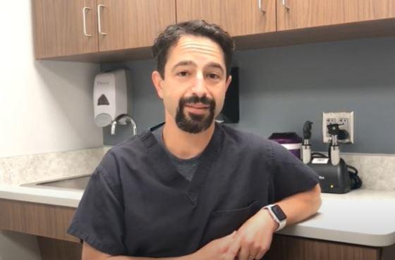 Dr. Zach Borus, wearing black scrubs, looking at camera