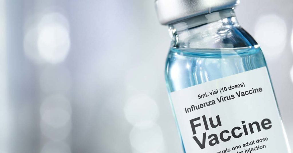 """vial of blue liquid inside with words """"flu vaccine"""" on label"""