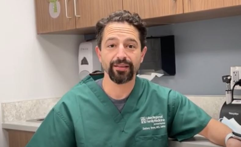 Dr. Zach Borus wearing green scrubs, sitting in an exam room, looking at camera.