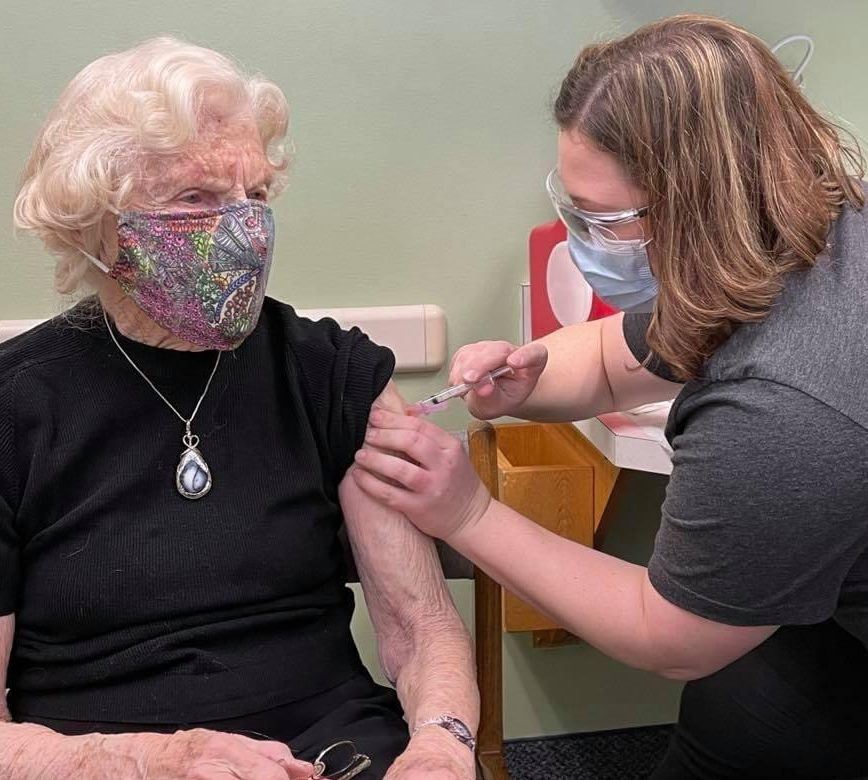 Woman wearing grey scrubs giving a COVID-19 injection to a woman with grey hair wearing a mask and a black tee shirt