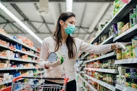 Woman with a white shirt, black hair, wearing a mask and in a grocery store