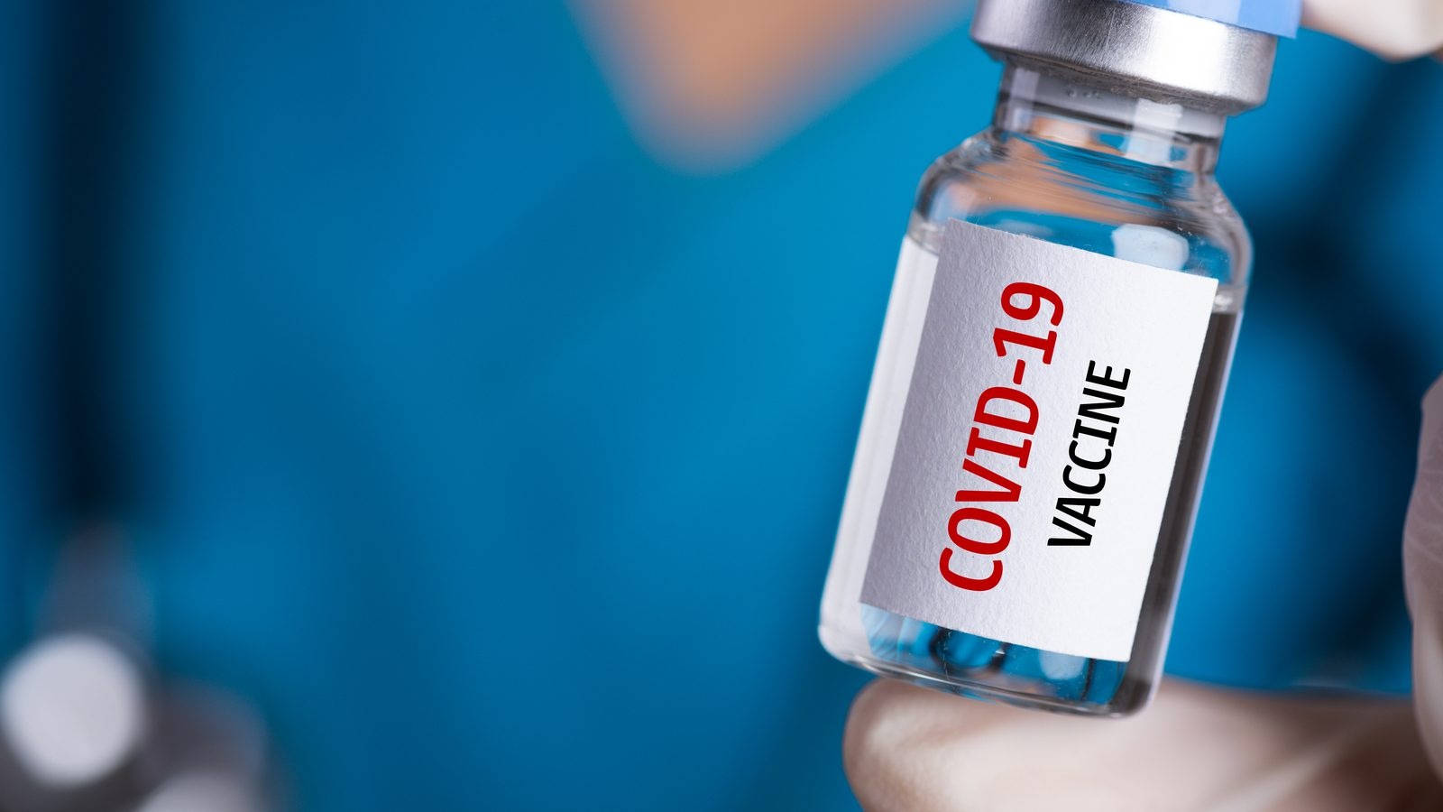 person in blue scrub shirt holding a covid-19 vaccine vial