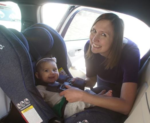 baby in car seat with mom strapping her in